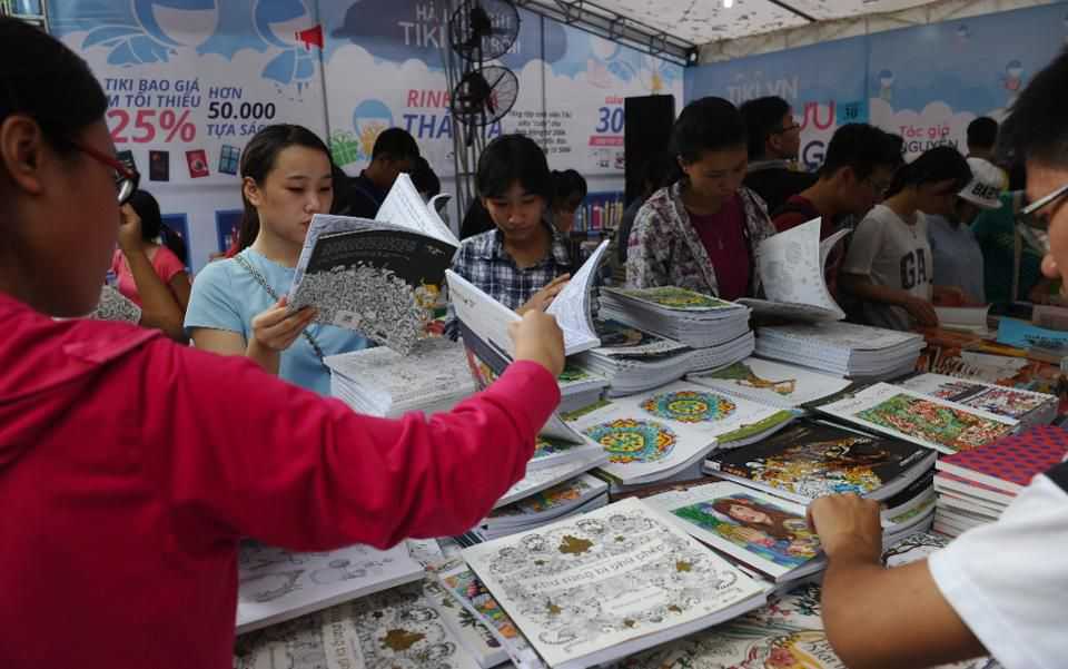Students look at books during a four-day book fair at a public park in downtown Hanoi on September 11, 2015